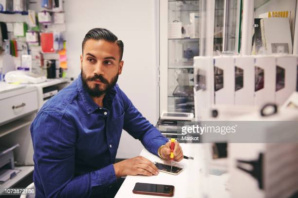 technician repairing mobile phone at table in workshop - electronics store stock photos and pictures