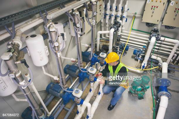 Technician repairing pipes in boiler room