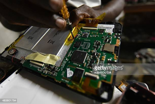 A technician repairs the hard disk of a mobile phone in a repair shop at the black market of the Koumassi quarter in Abidjan on August 12 2015 AFP...