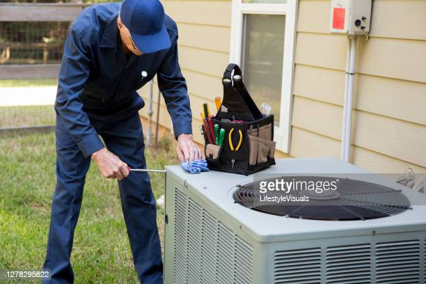 technician services outside ac units and generator. - air conditioner stock pictures, royalty-free photos & images