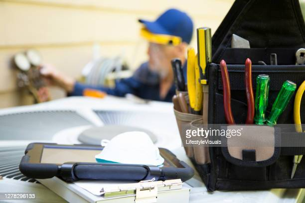 technician services outside ac units and generator. - repairing stock pictures, royalty-free photos & images