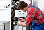 Technician servicing heating boiler