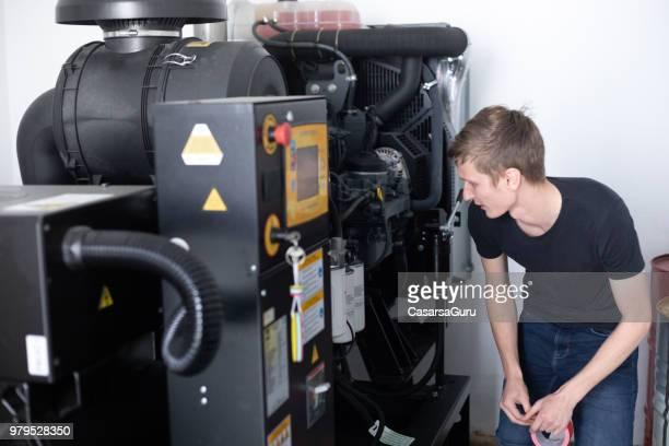 IT Technician Servicing Supercomputer Backup Generator