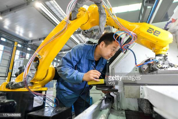 Technician sets up a robotic arm on the production line of luminaire housing at a smart factory of Zhejiang Hpwinner Scientific Company Limited on...