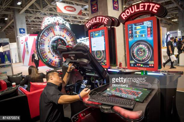 A technician sets up an electronic roulette machine manufactured by Interblock dd during the Macau Gaming Show in Macau China on Tuesday Nov 14 2017...