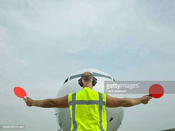 Technician signalling directions to aero plane