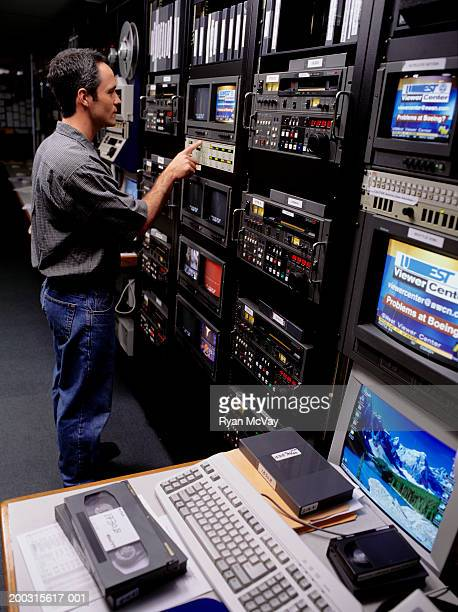 Technician standing at monitor of TV studio control room