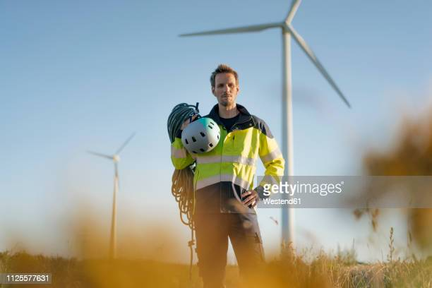technician standing in a field at a wind farm with climbing equipment - berufliche beschäftigung stock-fotos und bilder