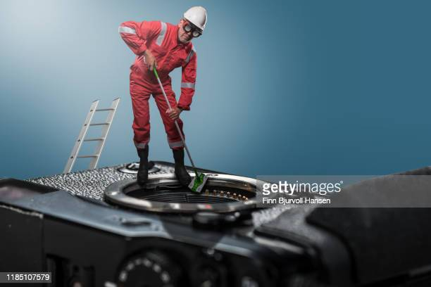 technician standing on camera cleaning camera sensor - finn bjurvoll - fotografias e filmes do acervo