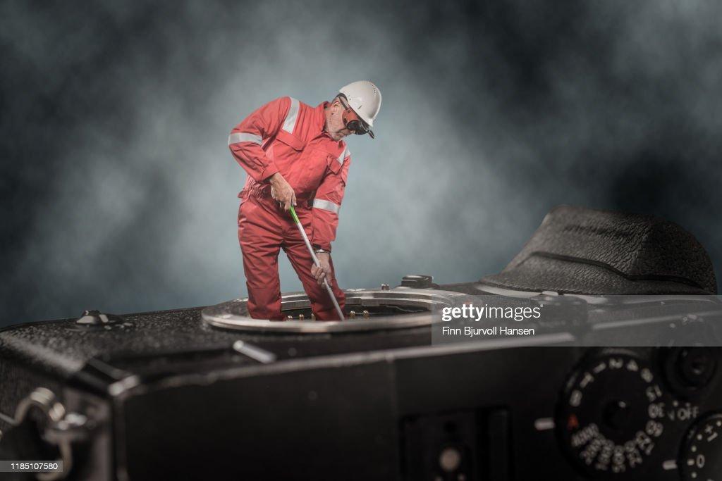 Technician standing on camera cleaning camera sensor : Stock Photo