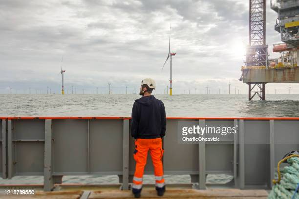 technician standing on transfer vessel deck in the morning and looking on offshore wind farm and offshore platform around - nautical vessel stock pictures, royalty-free photos & images