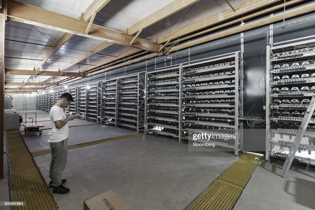 A technician stands in front of shelves of bitcoin mining machines at a mining facility operated by Bitmain Technologies Ltd. in Ordos, Inner Mongolia, China, on Friday, Aug. 11, 2017. Bitmainis one of the leading producers of bitcoin-mining equipment and also runs Antpool, a processing pool that combines individual miners from China and other countries, in addition to operating one of the largest digital currency mines in the world. Photographer: Qilai Shen/Bloomberg via Getty Images