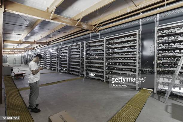 A technician stands in front of shelves of bitcoin mining machines at a mining facility operated by Bitmain Technologies Ltd in Ordos Inner Mongolia...