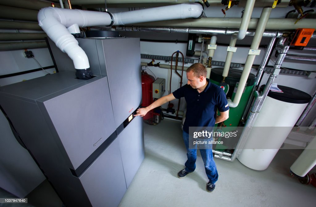 A technician stands next to the fuel cell heating system in