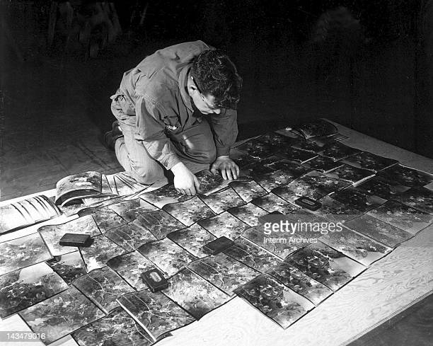 Technician Third Grade James Ellis of the 660th Engineers lays out photographs to check their sequence Kew Gardens England January 11 1943