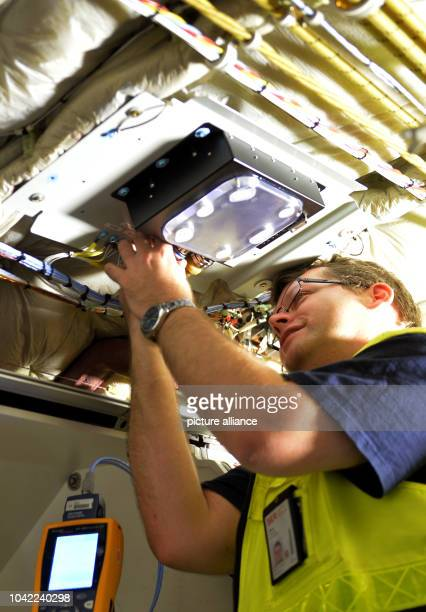 Technician Thomas Jaehne installs an Access Point device into an Airbus A321 at the Lufthansa hangar in Schoenefeld Germany 28 May 2014 The airline...