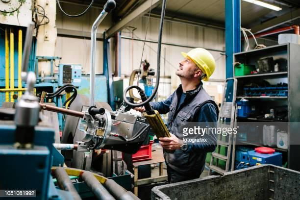 Techniker transportiert ein Schweißen Punkt-Zange mit einem Kran in einer Werkstatt