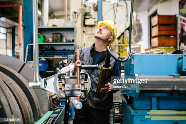 technician transports a welding point pliers with a crane in a workshop - mechanical engineering stock pictures, royalty-free photos & images
