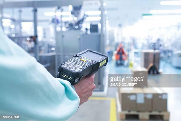 technician using a bar code reader in a pharmaceutical plant. - sigrid gombert stock-fotos und bilder