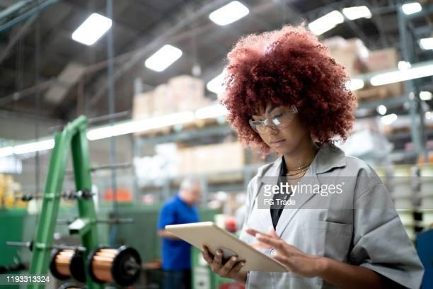técnico que utiliza una tableta digital mientras trabaja en la línea de producción de una fábrica - equidad de genero fotografías e imágenes de stock
