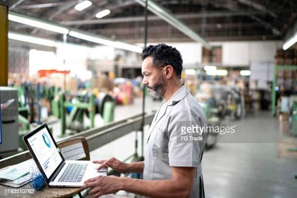 technicus die laptop gebruikt tijdens het werken in een fabriek - fabriek stockfoto's en -beelden