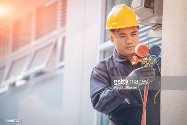 technician vacuum pump evacuates and checking new air conditioner. - pump dress shoe stock pictures, royalty-free photos & images
