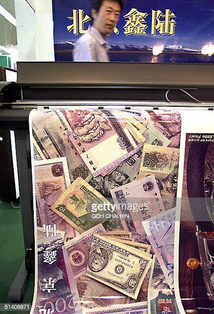 A technician waits as a poster of various currencies rolls out from a printer at the advertising material and equipment exhibition in Beijing 02...
