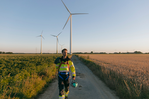 Technician walking on field path at a wind farm with climbing equipment - gettyimageskorea
