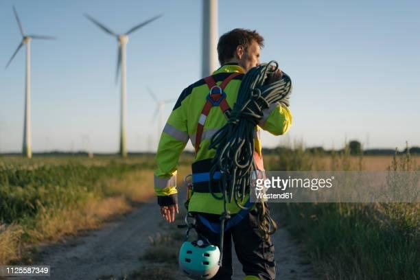 technician walking on field path at a wind farm with climbing equipment - energie stock-fotos und bilder