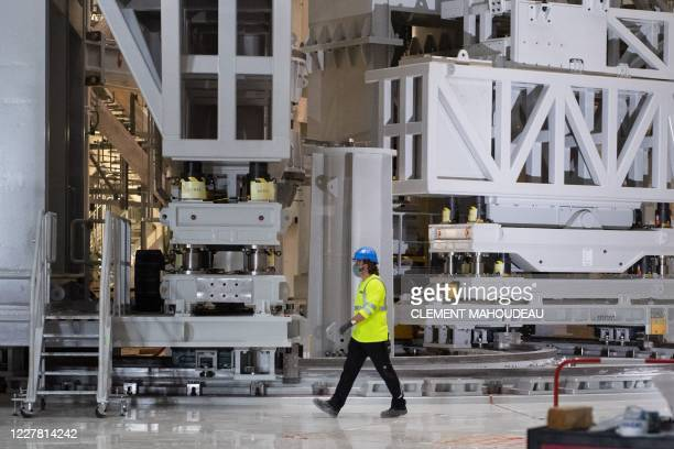 Technician walks in front of a pre-assembly gantry constructed by South Korea which will be used to assemble vacuum chamber sectors with vertical...