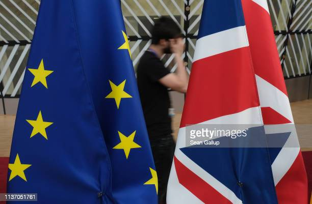 Technician walks past the flags of the United Kingdom and the European Union in the Europa building of the European Council one day prior to a summit...