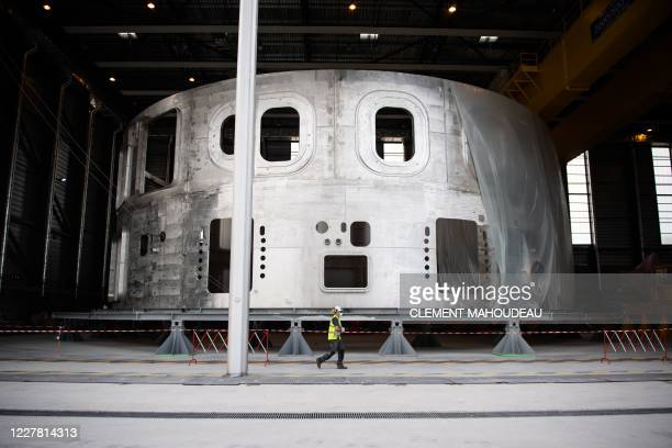 Technician walks past the lower cyclinder of the cryostat, which provides the high vacuum, ultra-cool environment for the vacuum vessel and the...