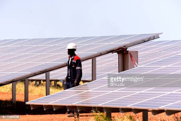 A technician walks through solar panels on October 22 2016 during the opening ceremony of a new photovoltaic energy production site in Bokhol Senegal...