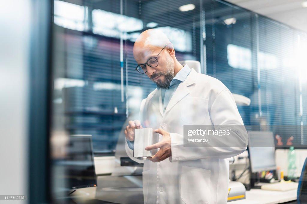 Technician wearing lab coat examining workpiece : Stock-Foto