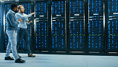 IT Technician with a Laptop Computer and Black Male Engineer Colleague are Talking in Data Center while Walking Next to Server Racks. Running Diagnostics or Doing Maintenance Work.