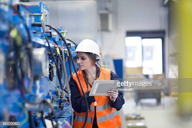 Technician with reflective vest in factory hall inspecting machine with digital tablet