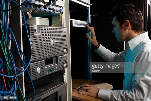 O técnico a trabalhar no computador consola na sala de equipamento