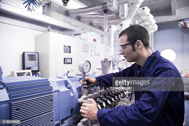 Technician working in a technical room looking at gauge