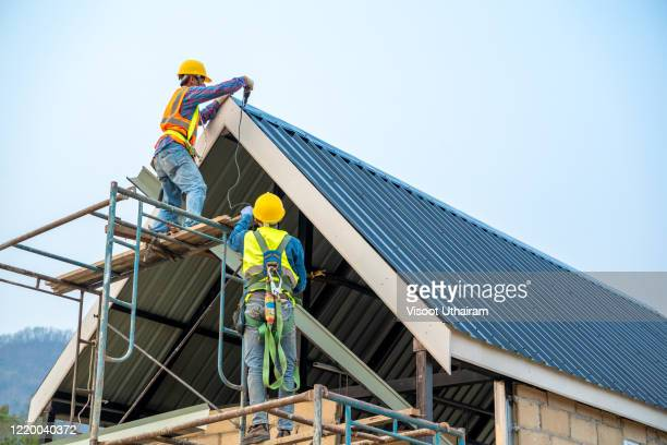 technician working on roof metal cheese in construction site. - roof stock pictures, royalty-free photos & images