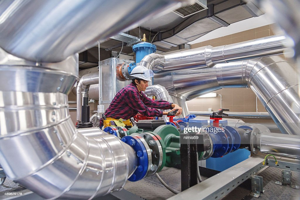 Technician working on valve in factory or utility : Stock Photo