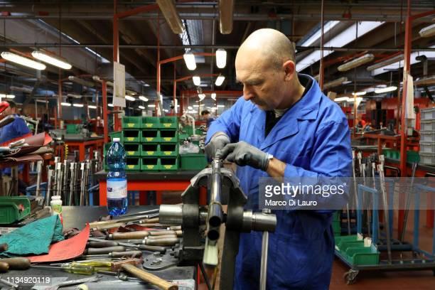 A technician works on a gun barrel on April 4 2019 at the Perazzi Armi factory in Botticino Mattina a village in the outskirt of the city of Brescia...