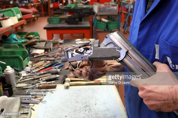 A technician works on the components of a shotgun on April 4 2019 at the Perazzi Armi factory in Botticino Mattina a village in the outskirt of the...