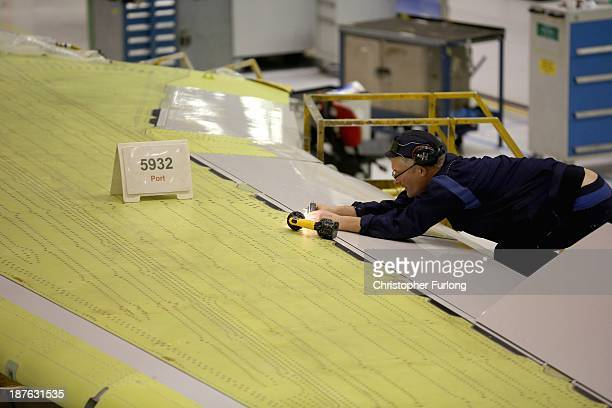 A technician works on the wing of an Airbus A320 during construction at the Airbus SAS factory on November 7 2013 in Broughton United Kingdom The...