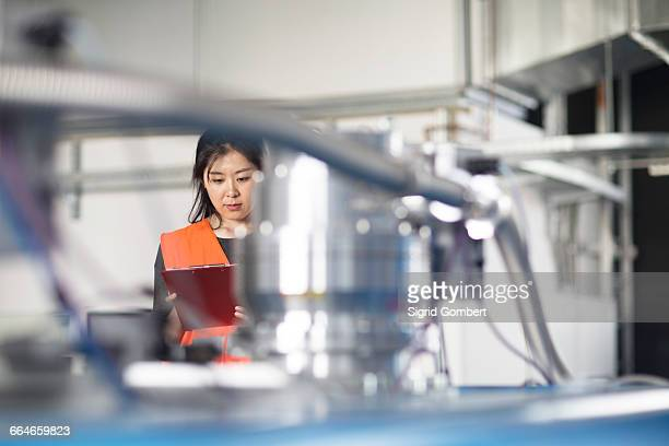 technician writing on clipboard in factory - sigrid gombert stock pictures, royalty-free photos & images