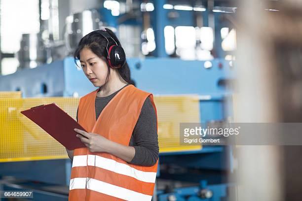 technician writing on clipboard in factory - sigrid gombert stock-fotos und bilder
