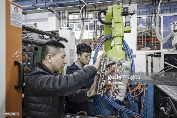 Technicians adjust an industrial robot manufactured by the EDeodar Robot Equipment Co a whollyowned subsidiary of Ningbo Techmation Co as it stands...