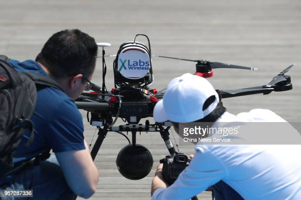 Technicians adjust an unmanned aerial vehicle carrying a 5G communication technology module before its takeoff along the Huangpu River on May 10 2018...