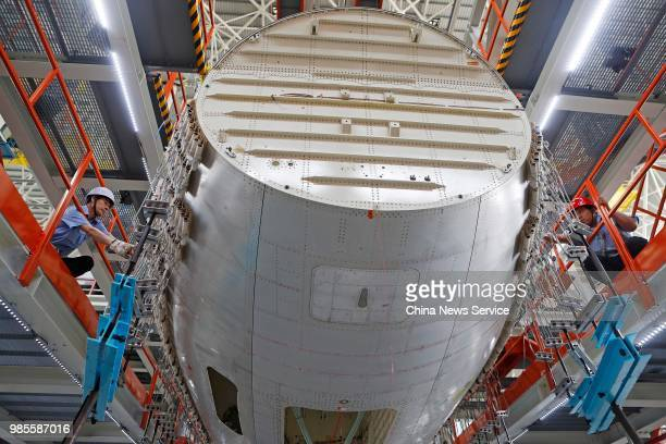 Technicians adjust China's first domestically made C919 passenger jet before its trial flight on June 25 2018 in Shanghai China The C919 aircraft...