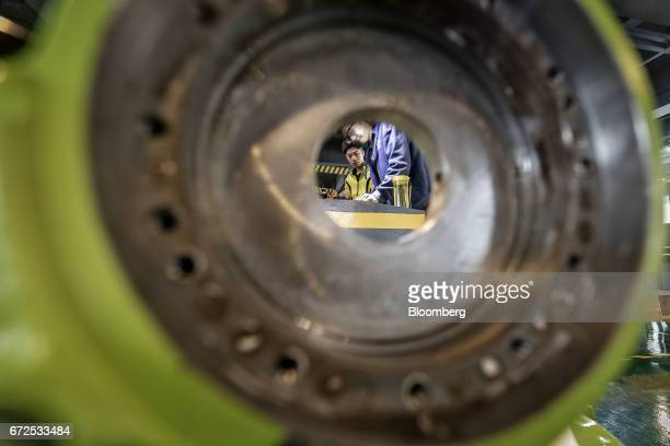 Technicians assemble a component of an industrial robot at a factory operated by EDeodar Robot Equipment Co a whollyowned subsidiary of Ningbo...
