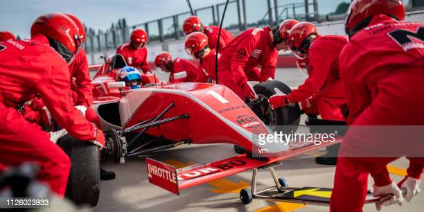 technicians changing tires during formula pit stop - pit stop stock pictures, royalty-free photos & images